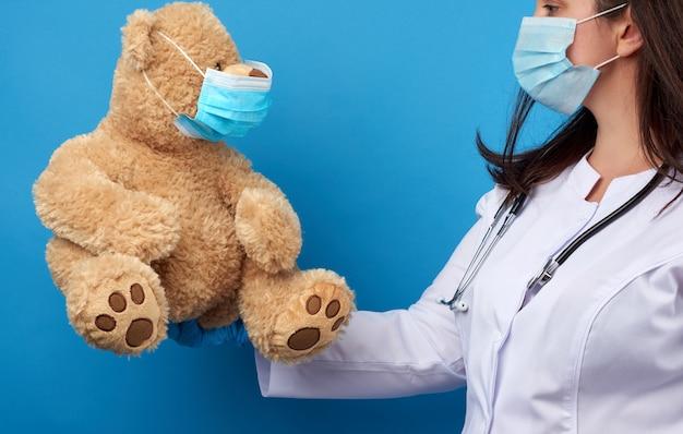 O pediatra do doutor da mulher prende o urso de peluche marrom disponivel na máscara descartável médica branca, conceito de impedir epidemias