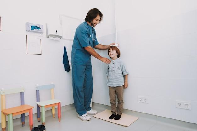 O pediatra mede o exame regular da altura das crianças.