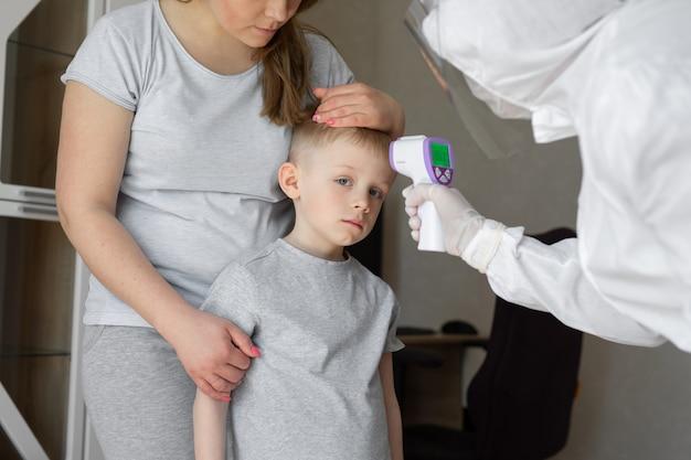 O pediatra ou o médico verifica a temperatura corporal do menino em idade elementar usando a arma infravermelha do termômetro da testa quanto a sintomas de vírus - conceito epidêmico de surto de coronavírus