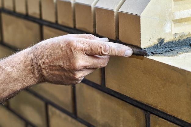 O pedreiro constrói uma nova cerca com tijolos de frente e alinhamentos de junta entre tijolos