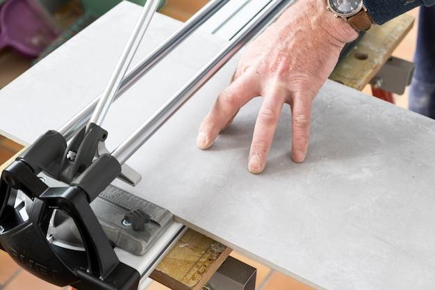 O pedreiro corta uma telha cerâmica com um cortador de azulejo