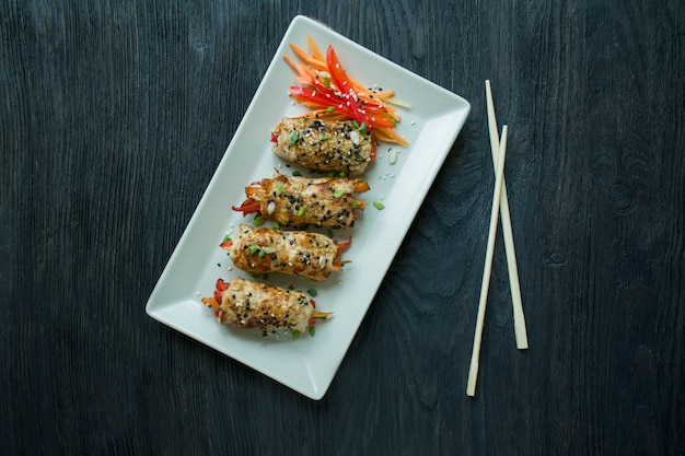 O peito de frango caseiro rola com verdes, fatias da cenoura, pimentão em uma placa retangular leve.