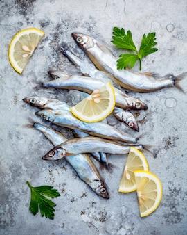 O peixe fresco de shishamo da captura eggs completamente o plano colocado no fundo gasto do metal.