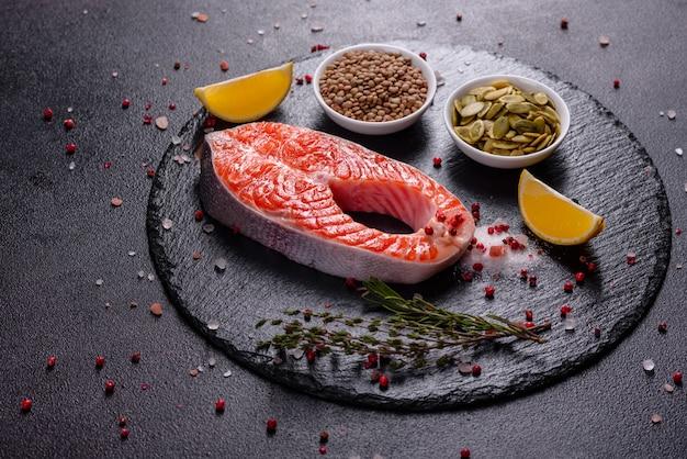 O peixe vermelho da truta crua serviu com ervas e limão e azeite. cozinhando salmão. conceito de alimentação saudável