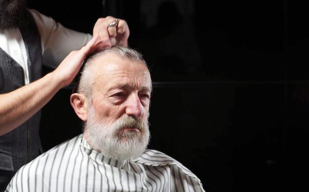 O pensionista de cabelos grisalhos está sentado em uma barbearia, uma barbearia no corte de cabelo. um barbeiro corta o cabelo de um homem idoso, um homem envelhecido
