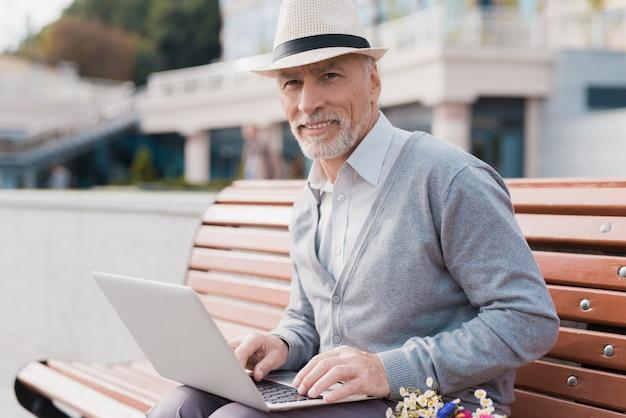 O pensionista senta no banco e trabalha atrás do laptop.