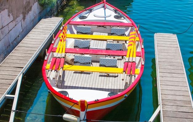 O pequeno barco colorido estacionado no cais de madeira.