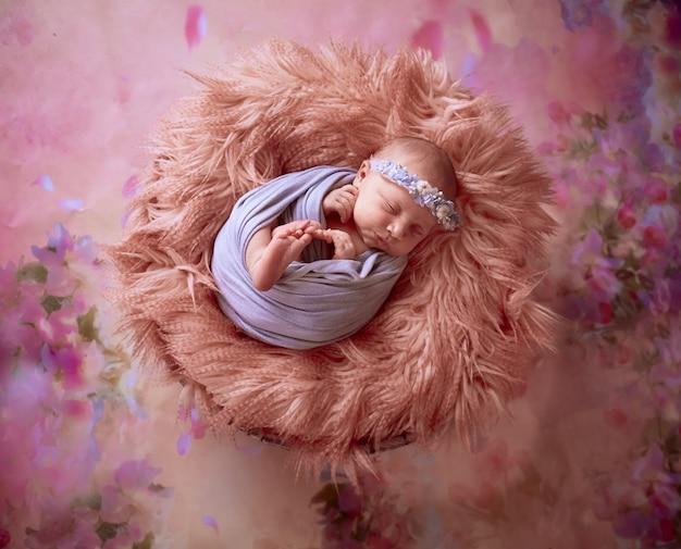 O pequeno bebê encontra-se no cesto com manta