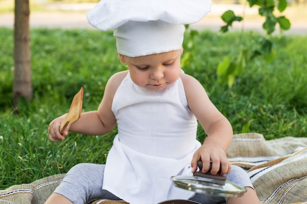 O pequeno chef cozinha o almoço em um piquenique ao ar livre. filho bonito em um terno de cozinheiro com panela e espátula de cozinha na parede verde da natureza