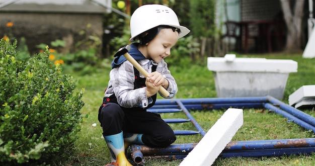 O pequeno construtor de capacete branco bate e bate em um pedaço de isopor com um martelo