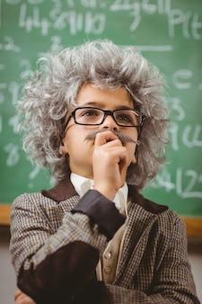 O pequeno einstein pensa na frente do quadro na sala de aula