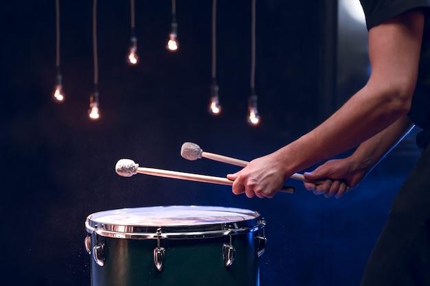 O percussionista toca paus no chão em uma sala escura com bela iluminação. conceito de concerto e performance.