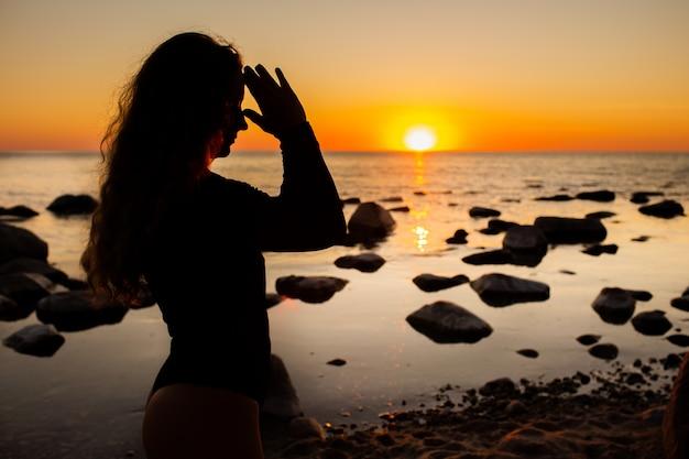 O perfil da jovem mulher que relaxa na praia, meditando com mãos em namaste gesticula no por do sol ou no nascer do sol, fim acima, silhueta.