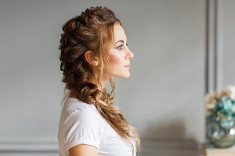 O perfil da menina bonita nova no fundo cinzento da parede.