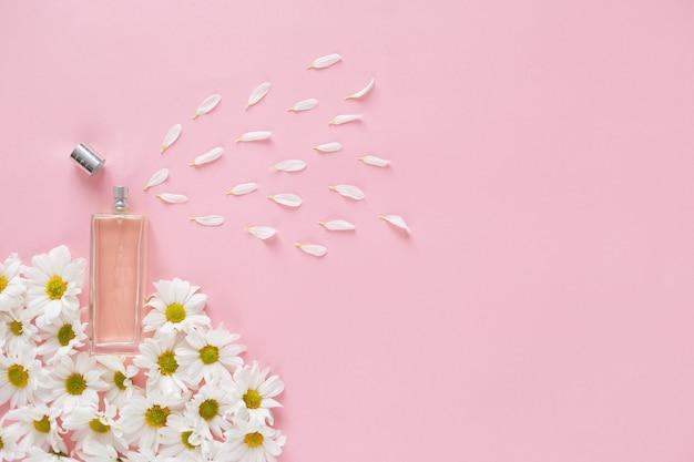 O perfume fresco da primavera espalha pétalas de flores. metáfora do aroma floral. frasco de vidro com muitos botões de flores de margarida em fundo rosa. vista superior, configuração plana