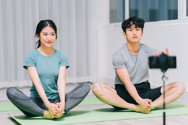 O personal trainer asiático está orientando os alunos sobre ioga e gravação de vídeo para ensinar ioga online