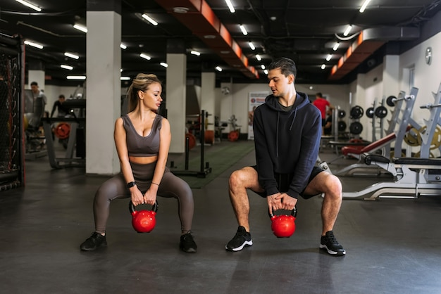 O personal trainer mostra a uma mulher como se agachar com um kettlebell em um ambiente esportivo.