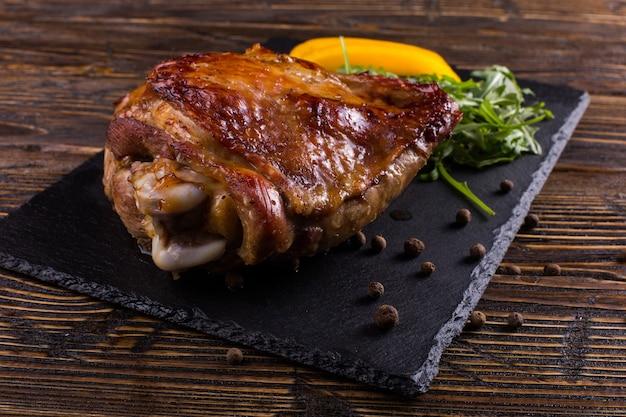 O peru da coxa cozeu no forno com as especiarias na placa de pedra preta. comida saudável. jantar de ação de graças.