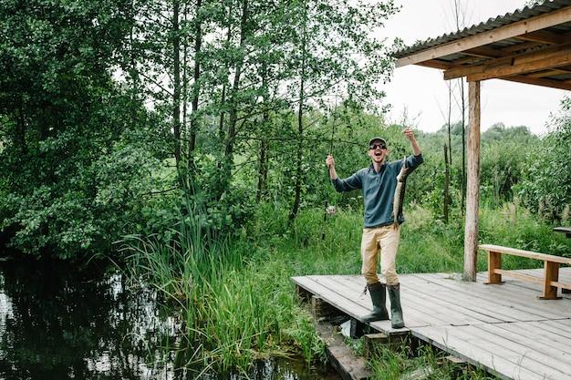 O pescador com vara de pescar pegou um peixe grande. boa pegada. peixe troféu.