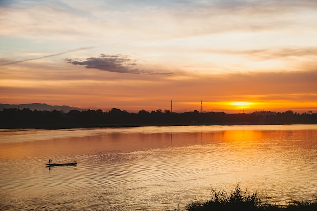 O pescador flutua em um lago no nascer do sol.