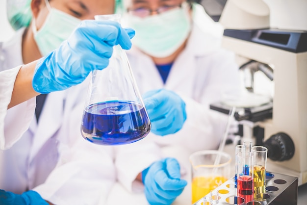 O pesquisador da jovem mulher que faz o equipamento da experiência e as experiências da ciência lubrificam o cientista de derramamento com a pesquisa de fatura amarela do tubo de ensaio no laboratório.