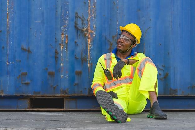 O pessoal de logística do capataz sentado relaxa no chão no transporte de contêineres