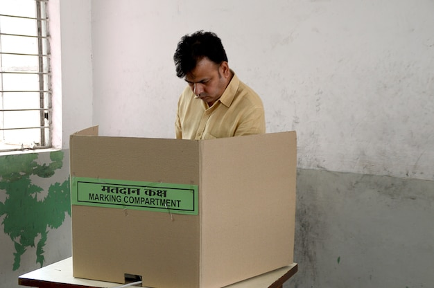 O pessoal e os oficiais de votação procuram o nome do eleitor na lista e concluem o processo de votação durante a eleição