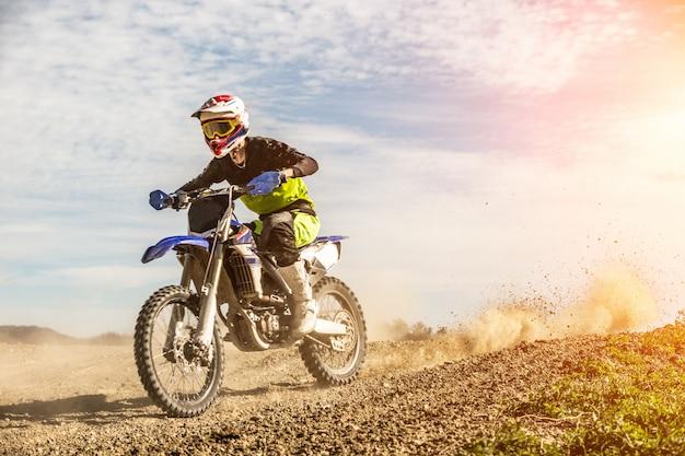 O piloto profissional da motocicleta do motocross conduz através da fumaça e da névoa sobre a trilha da estrada de terra.