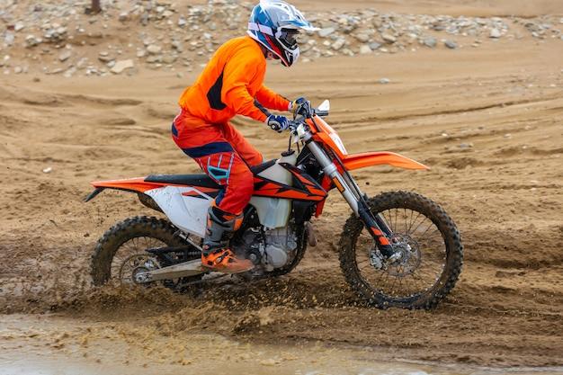 O piloto profissional da motocicleta do motocross conduz sobre a trilha da estrada.