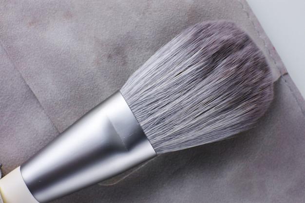 O pincel de maquiagem está em um estojo de camurça