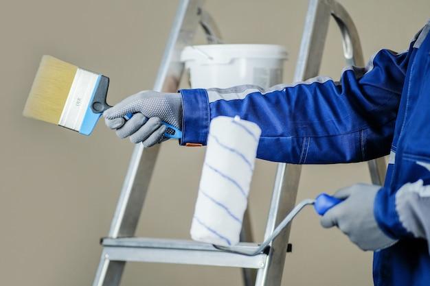O pintor de gesso está pronto para pintar a parede. nas mãos de um rolo e um pincel. uma escada e um balde de tinta ao fundo.