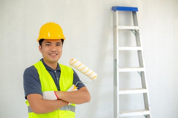 O pintor de sorriso asiático que guarda um rolo e um contexto de pintura tem uma escada de alumínio.
