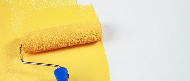 O pintor está pintando a parede interna de amarelo