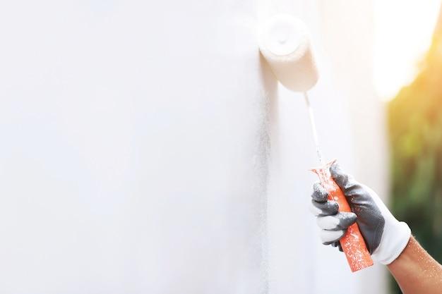 O pintor está pintando a parede interna de branco