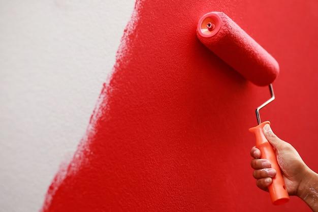 O pintor está pintando a parede interna de vermelho