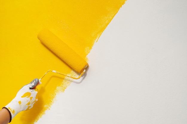 O pintor está pintando as paredes de amarelo com o interior da sala da casa.