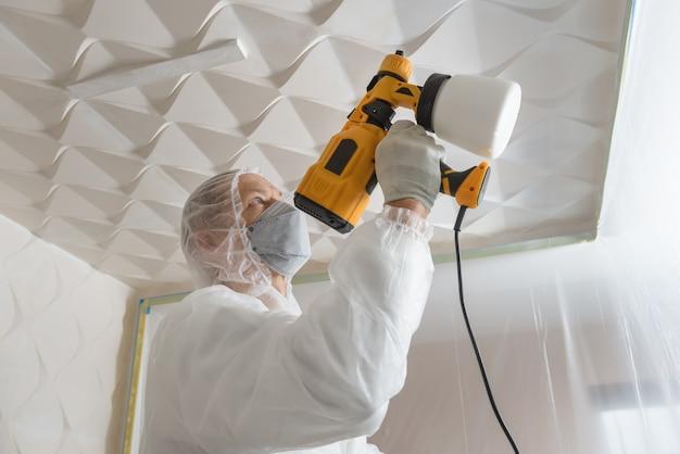O pintor está pintando um teto 3d com uma pistola de pulverização.
