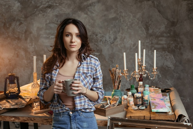 O pintor jovem bonita com uma xícara de café na oficina.