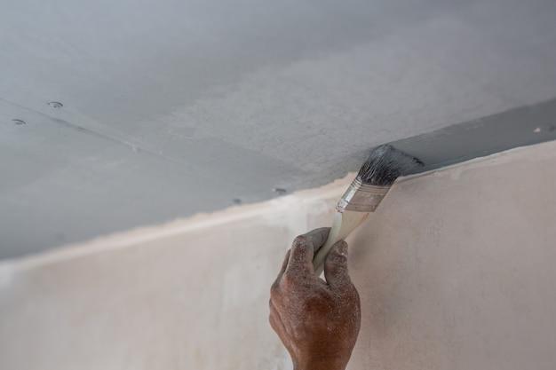 O pintor que está pintando na casa