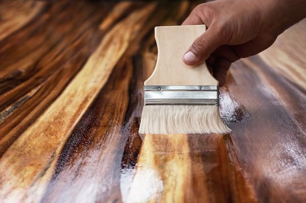 O pintor usa plotagens de pintura para revestir a madeira para beleza.