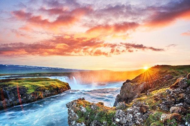 O pitoresco pôr do sol sobre paisagens e cachoeiras. kirkjufell mountain