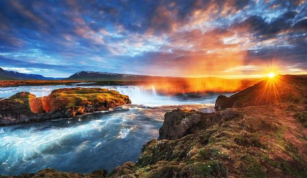 O pitoresco pôr do sol sobre paisagens e cachoeiras.