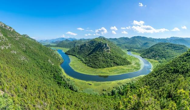 O pitoresco rio sinuoso flui entre montanhas verdes