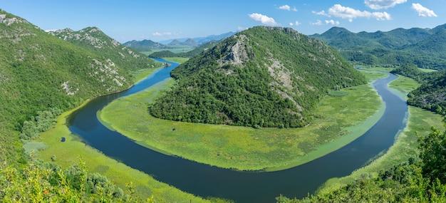 O pitoresco rio sinuoso flui entre montanhas verdes.
