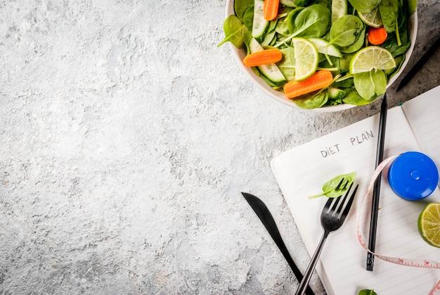 O plano da dieta perde o conceito, salada de legumes fresca com garfo, faca, bloco de notas