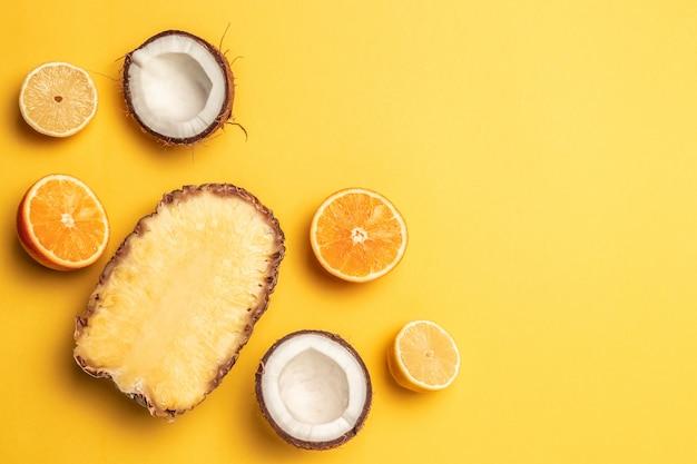 O plano da fruta tropical coloca com abacaxi, laranjas, limão e coco em um fundo pastel.