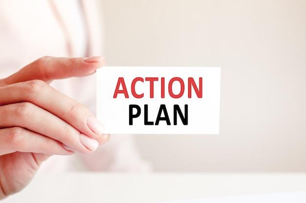 O plano de ação é escrito em um cartão de visita branco na mão de uma mulher