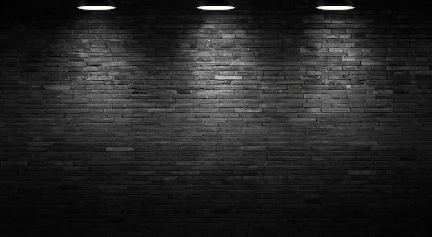 O plano de fundo da parede de tijolo preto e a luz da lâmpada.
