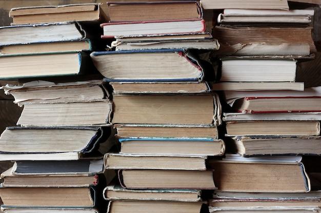 O plano de fundo dos livros. pilhas de livros antigos, virou as extremidades. biblioteca.