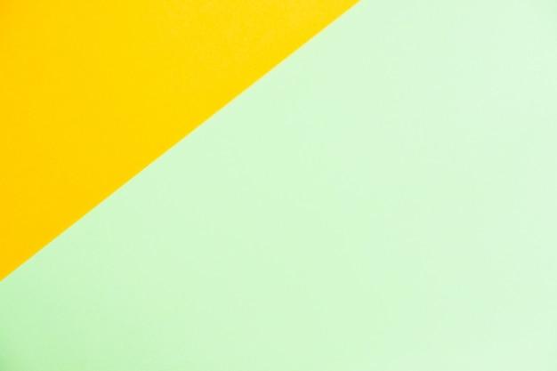 O plano de papel colorido da cor pastel coloca a vista superior, a textura do fundo, a laranja e o verde.